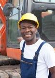 Travailleur de la construction africain avec l'excavatrice rouge au chantier de construction Images stock