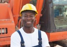 Travailleur de la construction africain riant avec l'excavatrice rouge Images stock