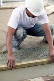 Travailleur de la construction aplatissant la dalle Image stock