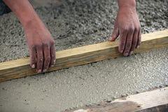 Travailleur de la construction aplatissant la dalle Image libre de droits