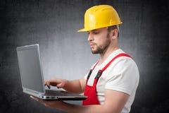 Travailleur de la construction avec l'ordinateur portatif photographie stock