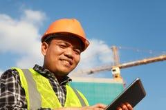 Travailleur de la construction avec le comprimé numérique Photo stock