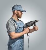Travailleur de la construction avec le foret sur le fond d'isolement Photo stock