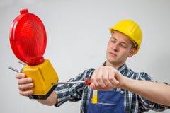 Travailleur de la construction avec une site-lampe rouge de construction Photo stock