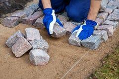 Travailleur de la construction de chemin de jardin étendant les machines à paver en pierre de granit photographie stock