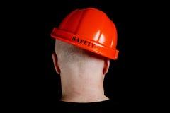 Travailleur de la construction dans le casque antichoc avec une sécurité d'inscription Photo stock