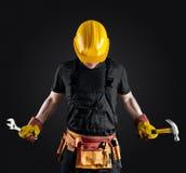 Travailleur de la construction dans le casque avec le marteau et la clé Image stock