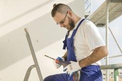 Travailleur de la construction dans le vêtement de travail, les gants protecteurs et un casque sur le site Photos libres de droits