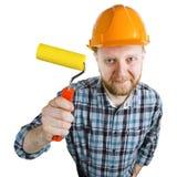 Travailleur de la construction dans un casque avec un rouleau de peinture photos libres de droits