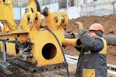 Travailleur de la construction de sexe masculin sur un travail de chantier de construction réparant s Images stock