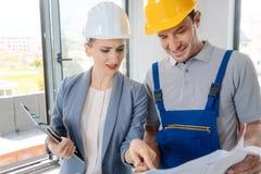 Travailleur de la construction et architecte regardant le plan sur le site images libres de droits