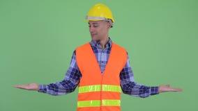 Travailleur de la construction ethnique multi heureux d'homme comparant quelque chose banque de vidéos