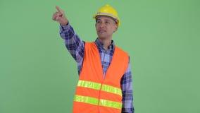 Travailleur de la construction ethnique multi heureux d'homme dirigeant le doigt banque de vidéos