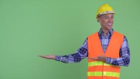 Travailleur de la construction ethnique multi heureux d'homme montrant quelque chose clips vidéos