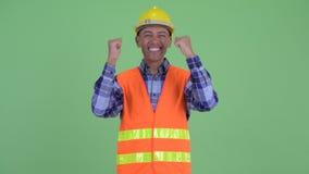 Travailleur de la construction ethnique multi heureux d'homme obtenant de bonnes nouvelles banque de vidéos