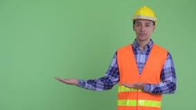 Travailleur de la construction ethnique multi soumis à une contrainte d'homme montrant quelque chose banque de vidéos