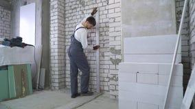Travailleur de la construction faisant des mesures avec le niveau de laser au chantier de construction clips vidéos