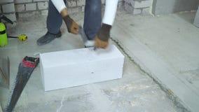 Travailleur de la construction faisant la majoration sur le bloc de béton aéré au chantier de construction banque de vidéos