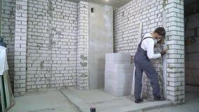 Travailleur de la construction faisant la majoration sur le mur selon le niveau de laser banque de vidéos