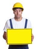 Travailleur de la construction latin naïf avec le signe Images libres de droits