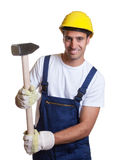 Travailleur de la construction latin puissant avec le marteau de forgeron images stock