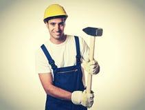Travailleur de la construction latin puissant avec le marteau de forgeron dans le vintage Photo libre de droits