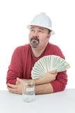 Travailleur de la construction malheureux se tenant sur l'argent d'impôts Photographie stock libre de droits