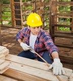 Travailleur de la construction Measuring Wooden Plank au site image stock