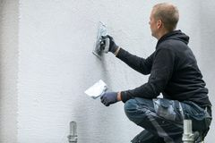 Travailleur de la construction mettant le plâtre décoratif sur l'extérieur de maison Image stock
