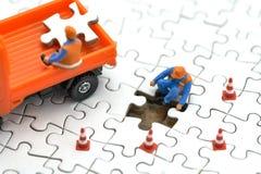 Travailleur de la construction miniature de personnes sur le puzzle blanc utilisation en tant que le concept d'affaires de fond e photographie stock libre de droits