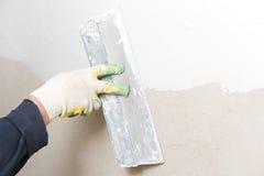 Travailleur de la construction plâtrant le mur de maison image stock