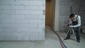 Travailleur de la construction plaçant le niveau de laser pour les murs de repérage au chantier de construction clips vidéos