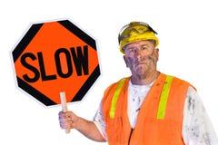 Travailleur de la construction retenant un signe lent Image stock
