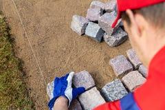 Travailleur de la construction de trottoir étendant le pavé rond de granit image stock