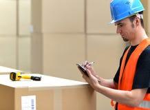 Travailleur de logistique - l'homme balaye des colis des marchandises et prépare le d photographie stock