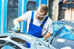 Travailleur de mécanicien automobile polissant la voiture de butoir Images stock