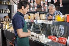 Travailleur de observation d'homme heureux coupant en tranches le fromage dans la boutique Images libres de droits