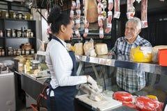 Travailleur de observation d'homme heureux coupant en tranches le fromage dans la boutique Photo libre de droits