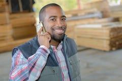 Travailleur de portrait au téléphone dans le woodyard photo stock