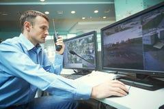 Travailleur de sécurité pendant la surveillance Système de surveillance visuel images stock