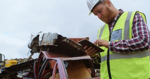 Travailleur de sexe masculin à l'aide du comprimé numérique dans l'entrepôt de ferraille 4k clips vidéos