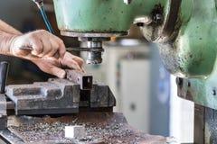 Travailleur de sexe masculin actionnant une machine de perceuse de coupeur de fraisage à l'intérieur d'une usine d'aluminiun photographie stock