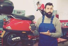 Travailleur de sexe masculin comptant la somme pour sa réparation Photographie stock libre de droits