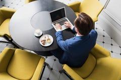Travailleur de sexe masculin concentré dactylographiant sur l'ordinateur portable pendant le petit déjeuner Image libre de droits