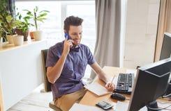 Travailleur de sexe masculin créatif heureux invitant le smarphone Photos stock