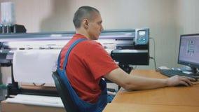 Travailleur de sexe masculin dans la typographie avec l'ordinateur devant la presse typographique photo stock