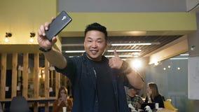 Travailleur de sexe masculin de hippie faisant le selfie au téléphone intelligent sur le fond moderne de bureau clips vidéos