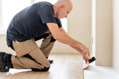 Travailleur de sexe masculin installant le nouveau plancher en stratifié en bois sur un plancher chaud d'aluminium de film systèm photos libres de droits
