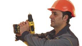 Travailleur de sexe masculin mûr de constrution posant avec une machine de foret banque de vidéos