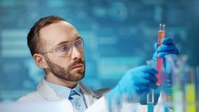 Travailleur de sexe masculin de scientifique faisant la substance de pharmacologie utilisant le becher au fond numérique de lumiè clips vidéos